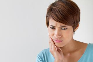 a woman holds her hand to her jaw | tmj treatment Columbia IL