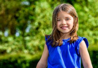 A girl smiles in front of a tree | Workman Family Dental