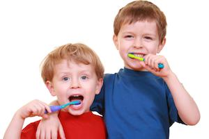Two boys brush their teeth infront of a white backdrop | Workman Family Dental