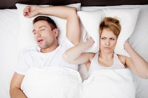 A woman covers her ears with her pillow as her husband snores next to her | Sleep Apnea Treatment Columbia IL