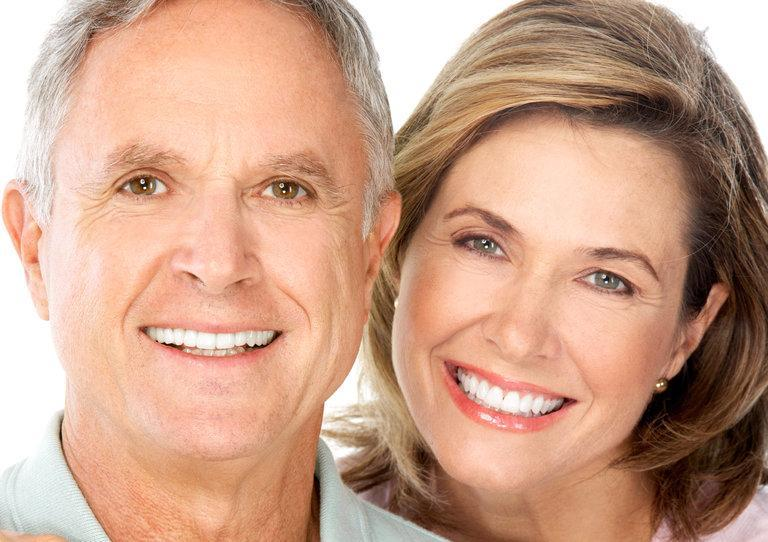 A couple smiles in front of a white backdrop | Dental Crowns Columbia IL